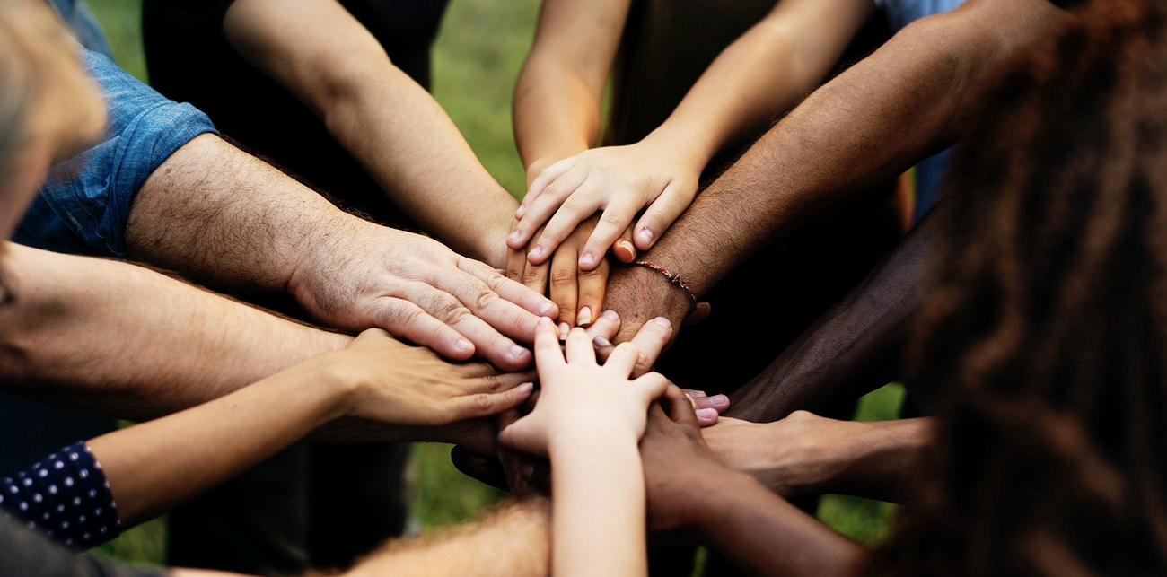 Image of diverse community with hands together